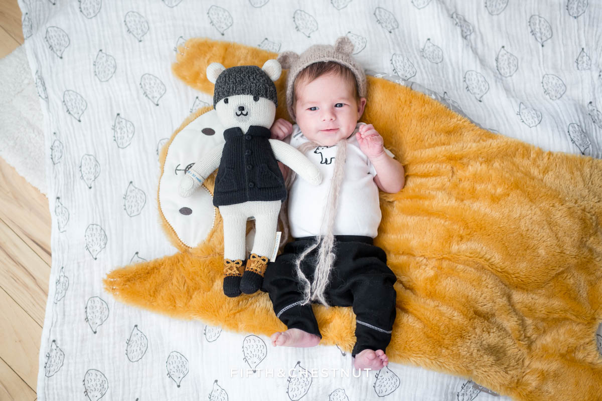 Baby boy wearing bear hat with Cuddle & Kind bear laying on fox blanket
