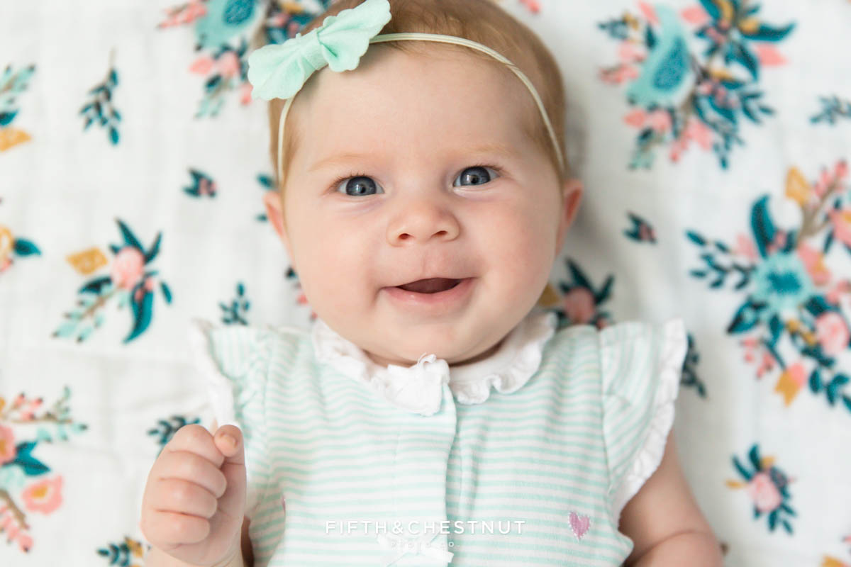 3 month old baby girl smiling at Reno Baby Photographer on a teal, pink and white muslin meadowlark blanket background