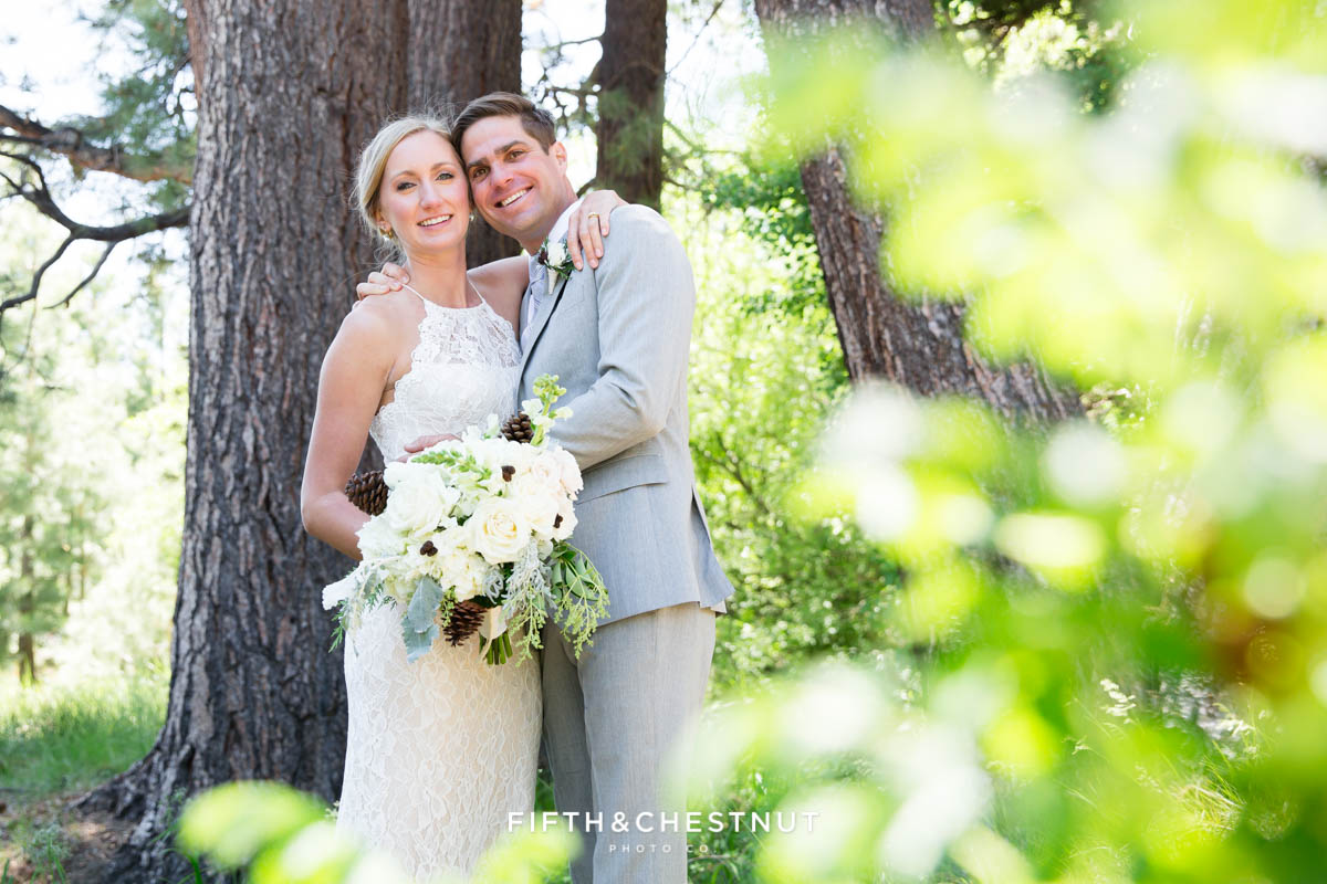 bride and groom embracing with leaves in the foreground