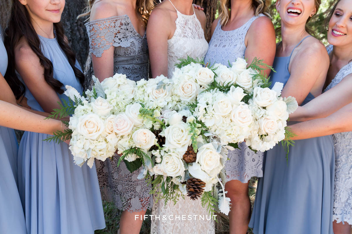 bride and bridesmaids in dusty blue show off their bouquets for a Tahoe wedding