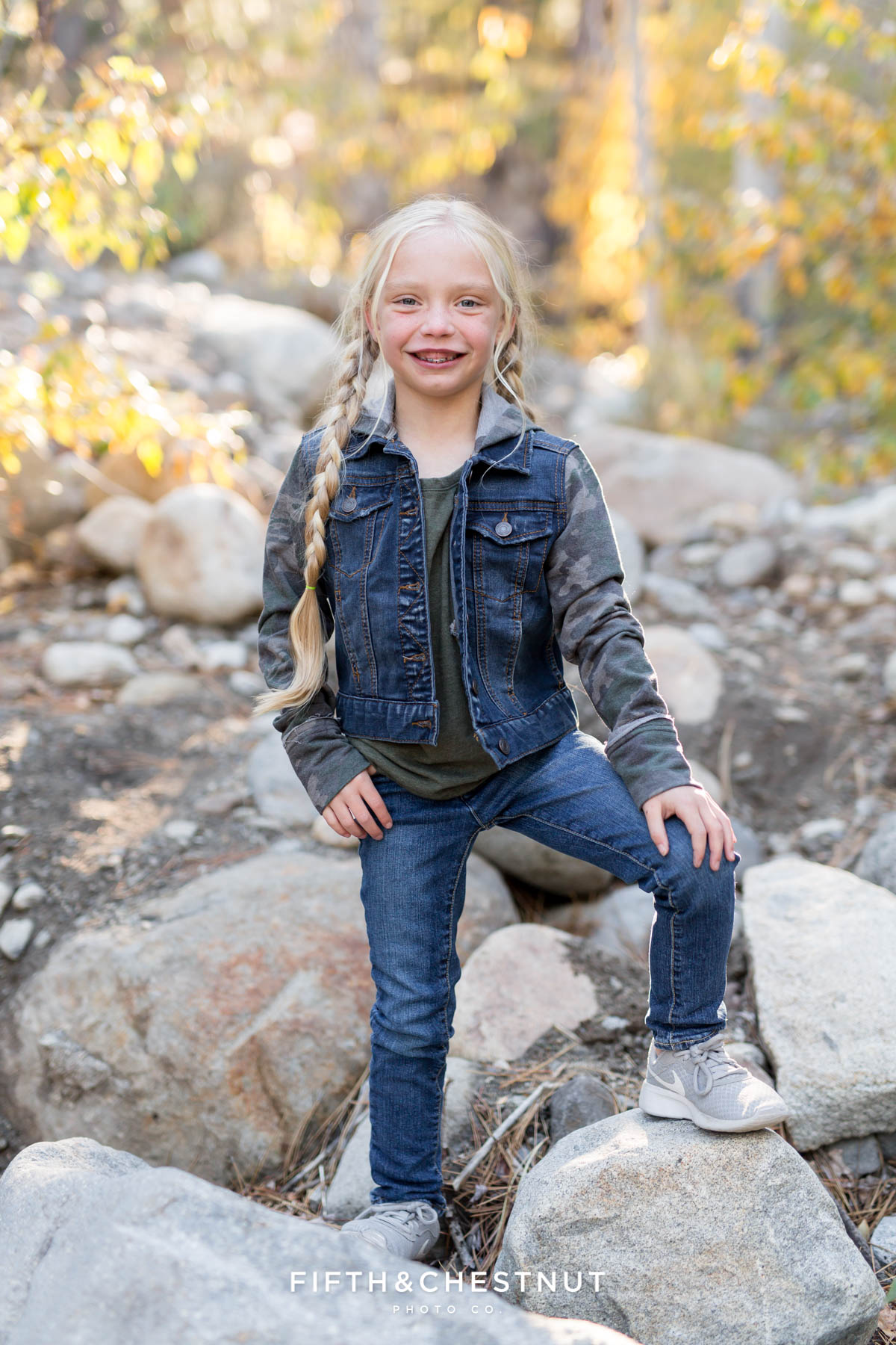 little girl wearing jean jacket poses on rocks for Galena Creek Reno fall portraits by Reno Family Photographer
