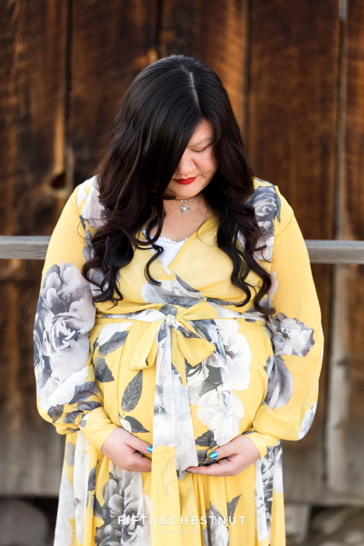 Pregnant woman in yellow and gray floral dress holds pregnant tummy while looking down surrounded by rustic western buildings in Reno, NV for maternity portraits by Reno Maternity Photographer