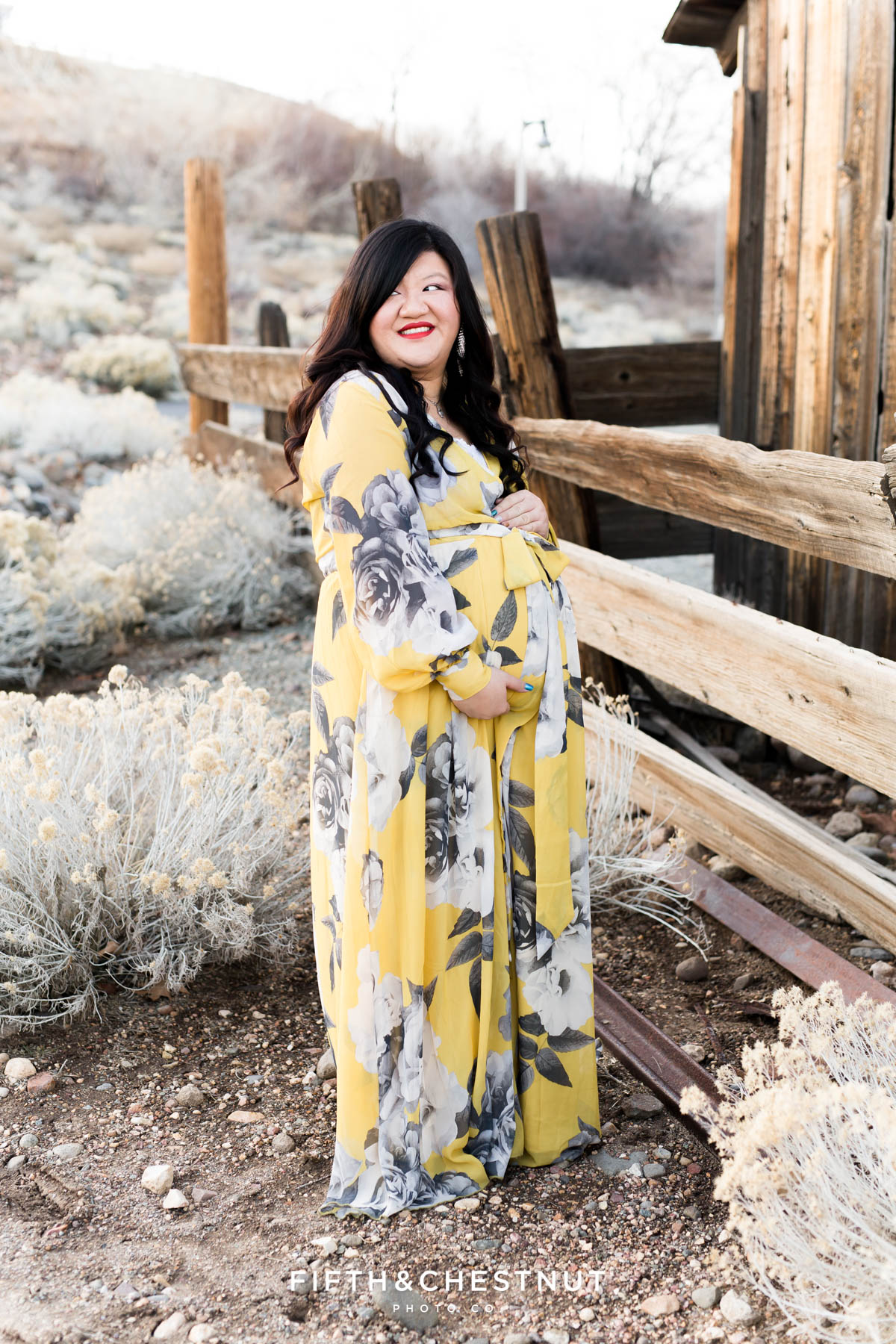 Pregnant woman in yellow and gray floral dress holds pregnant tummy while looking down surrounded by rustic fences and high desert foliage in Reno, NV for maternity portraits by Reno Maternity Photographer