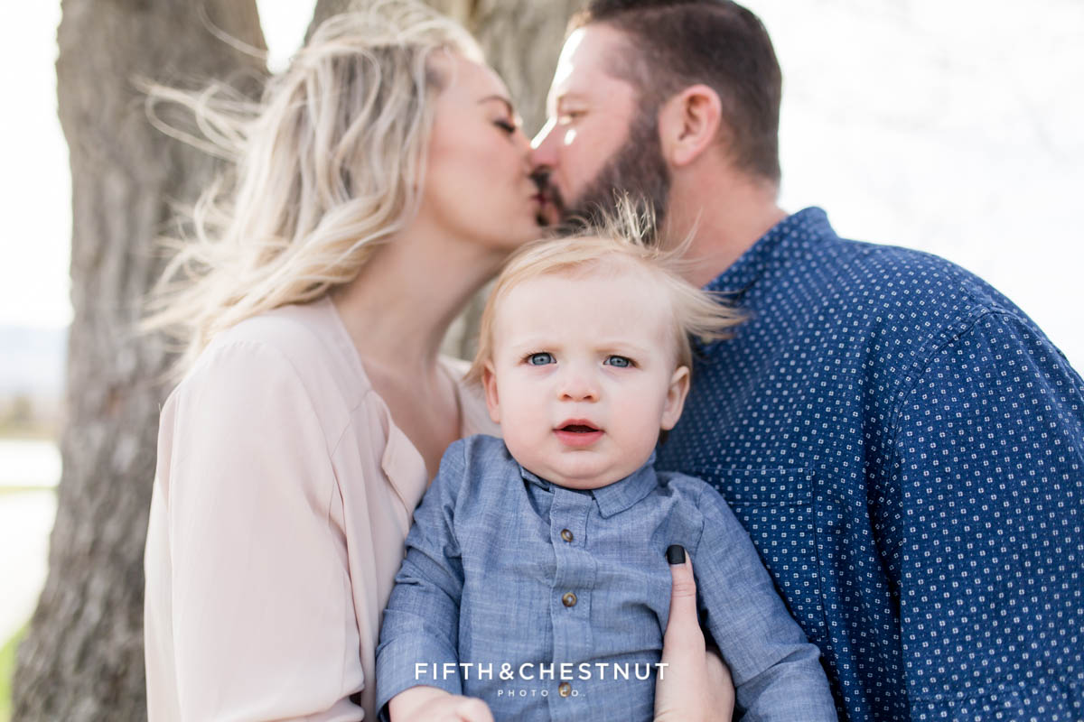 Focus on baby boy while mom and dad kiss in the background for Golf Themed One Year Photos by Reno Baby Photographer