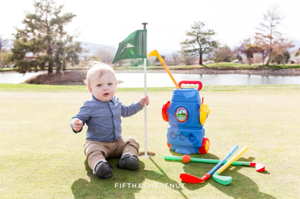 Baby boy holding flag on the green for his Golf Themed One Year Photos by Reno Baby Photographer surrounded by his toy golf clubs and golf balls on a sunny day