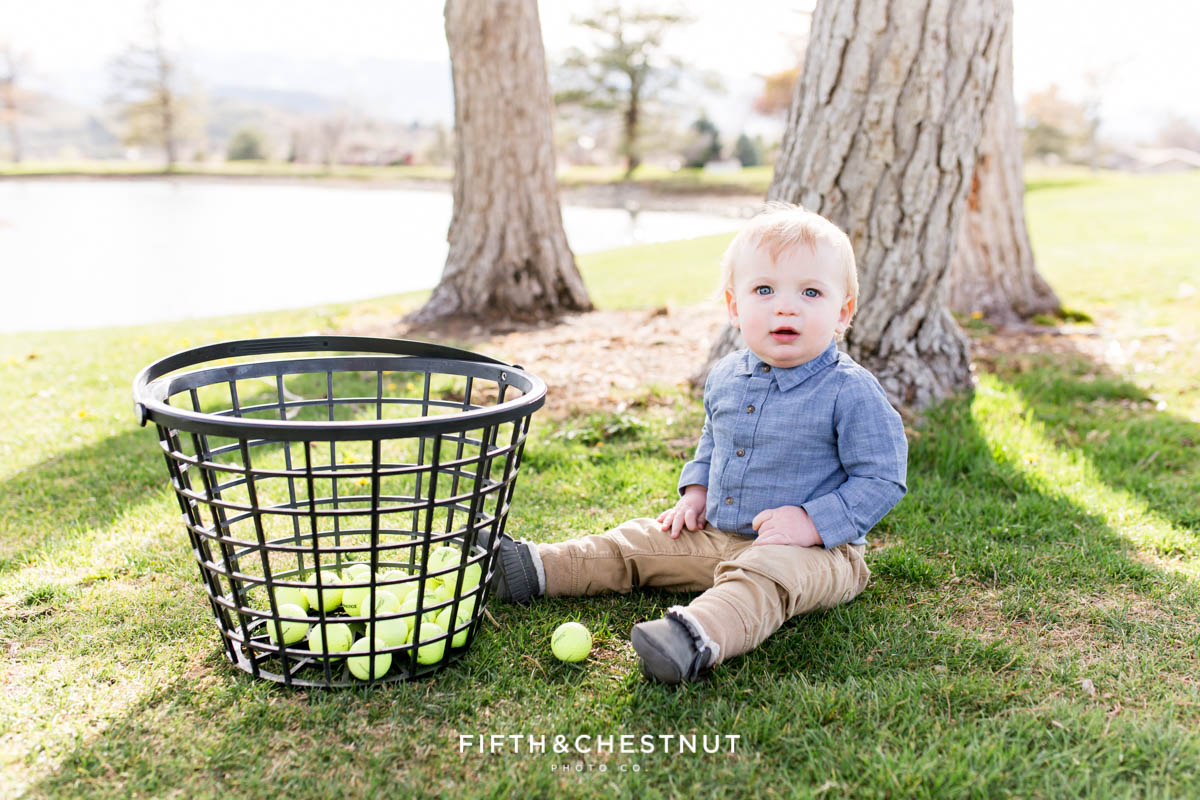 Baby boy posing with toy golf clubs and a basket of golf balls at Hidden Valley Country Club for his Golf Themed One Year Photos by Reno Baby Photographer