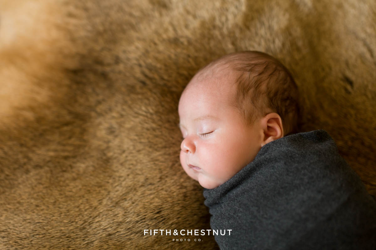 a newborn baby boy laying on an elk pelt while swaddled in gray stretchy fabric for his reno newborn photos by Reno Newborn Photographer