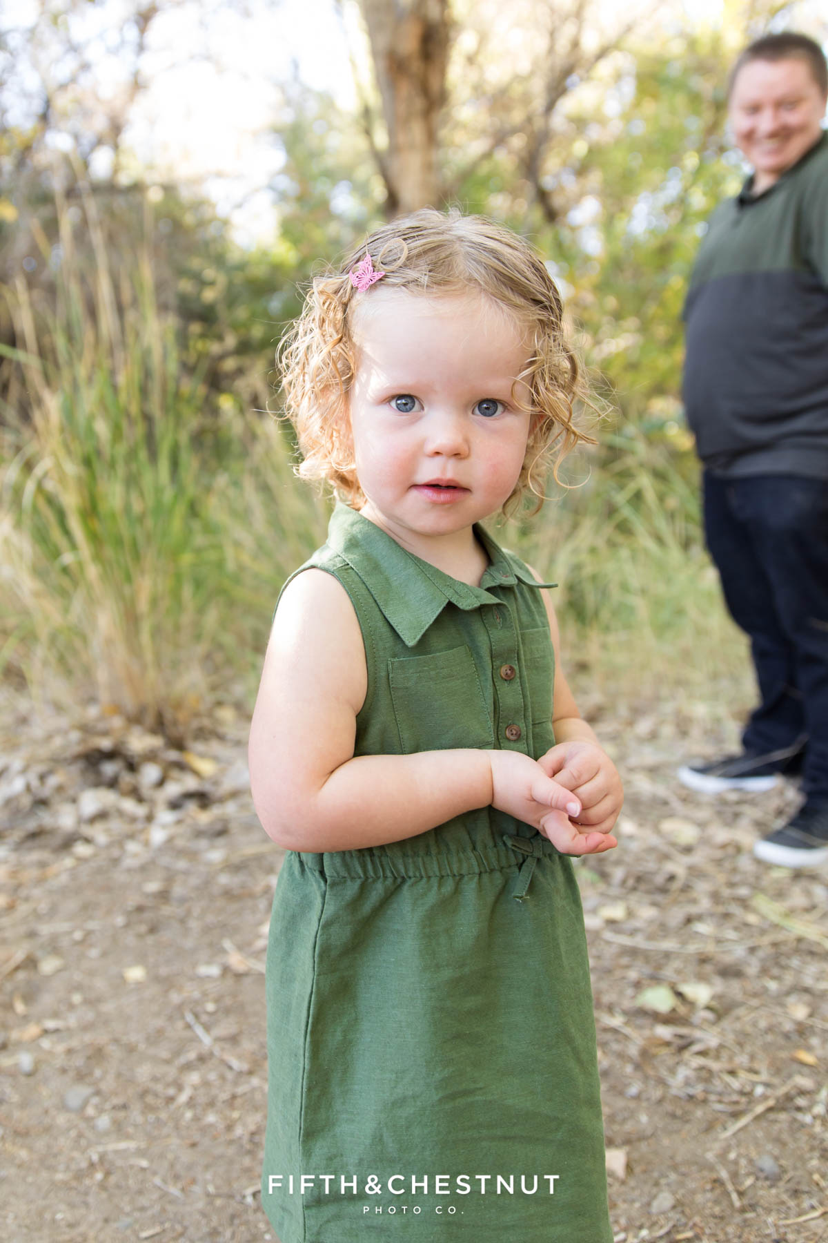 Child gazes at photographer during her earthtone family portraits in October in Reno