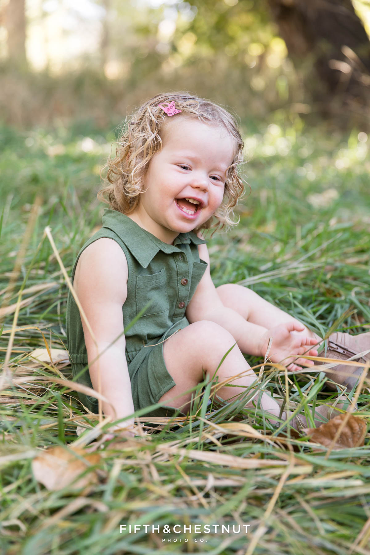 Girl sits in grass for earthtone family portraits at the Oxbow Nature Study