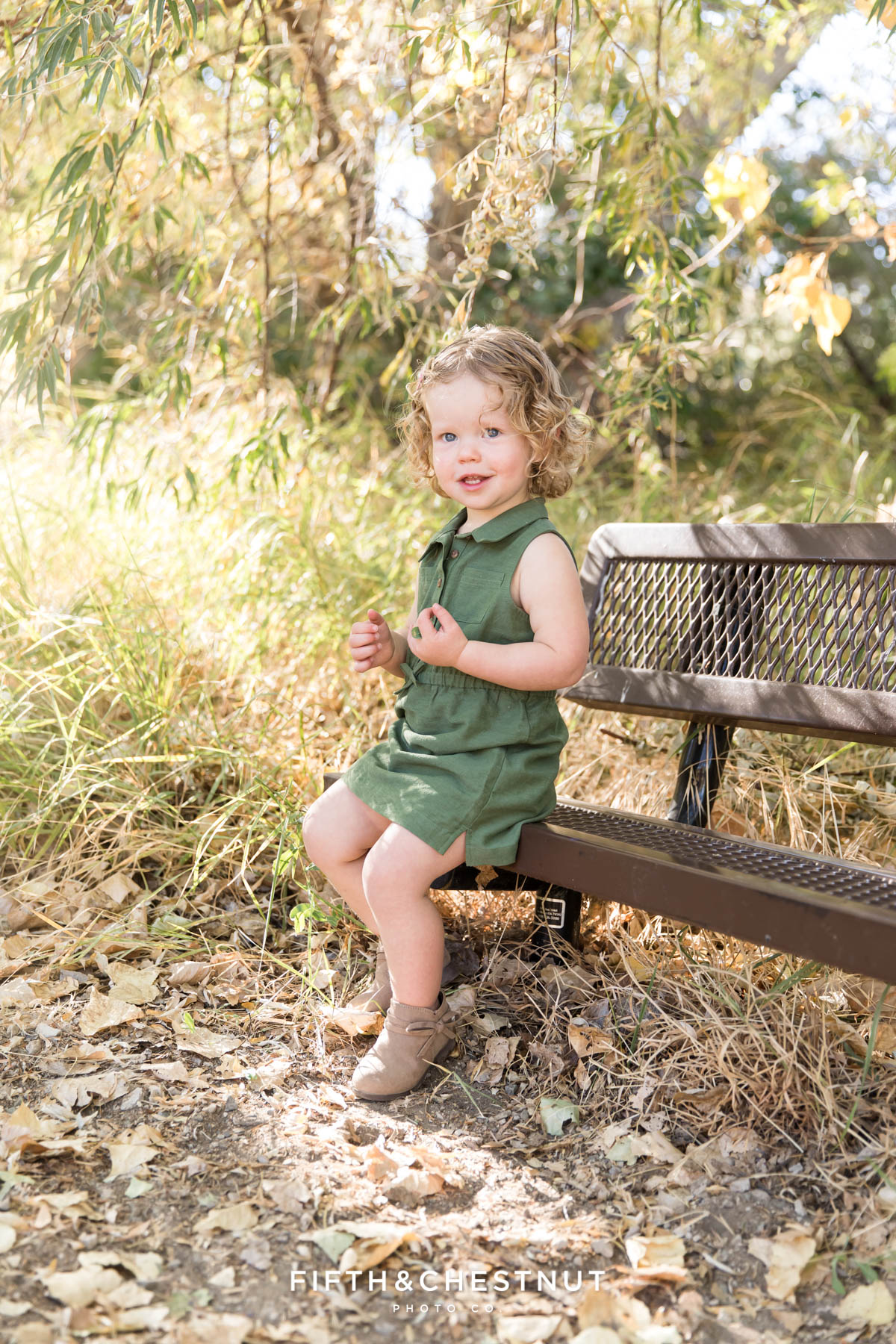 toddler sits on a bench at Oxbow Nature Study for photos by Reno Family Photographer