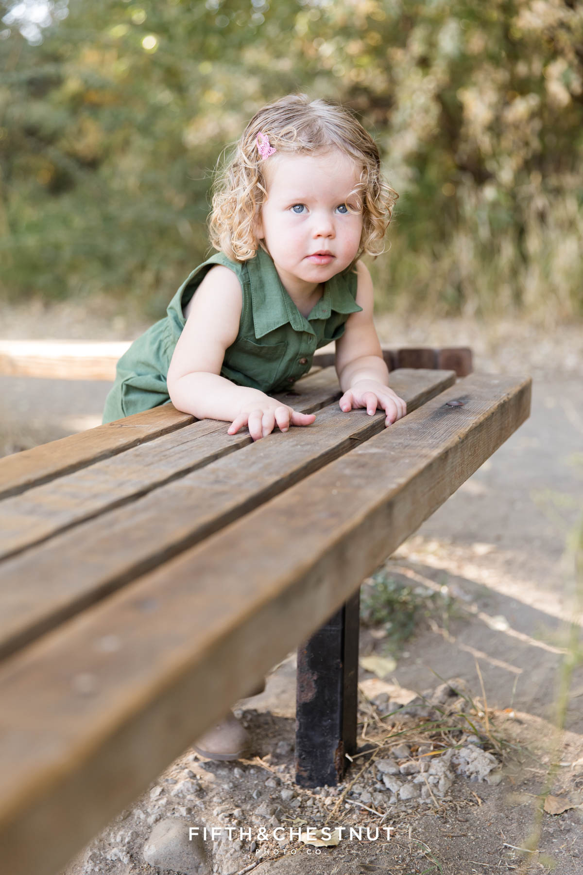 Toddler girl climbing on a bench wearing earthtone colored dress.