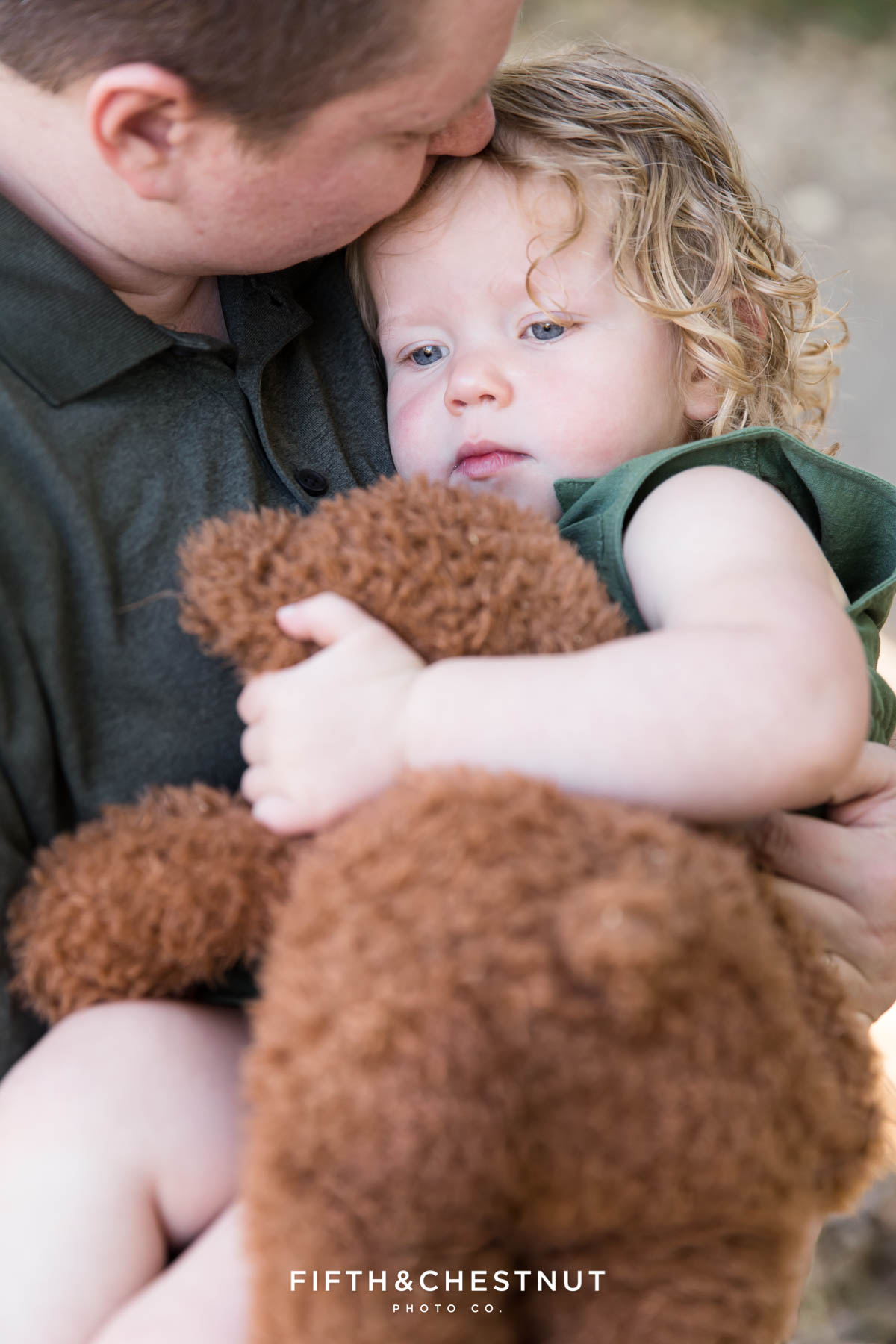 Mom kisses her daughter on the head as she holds her teddy bear