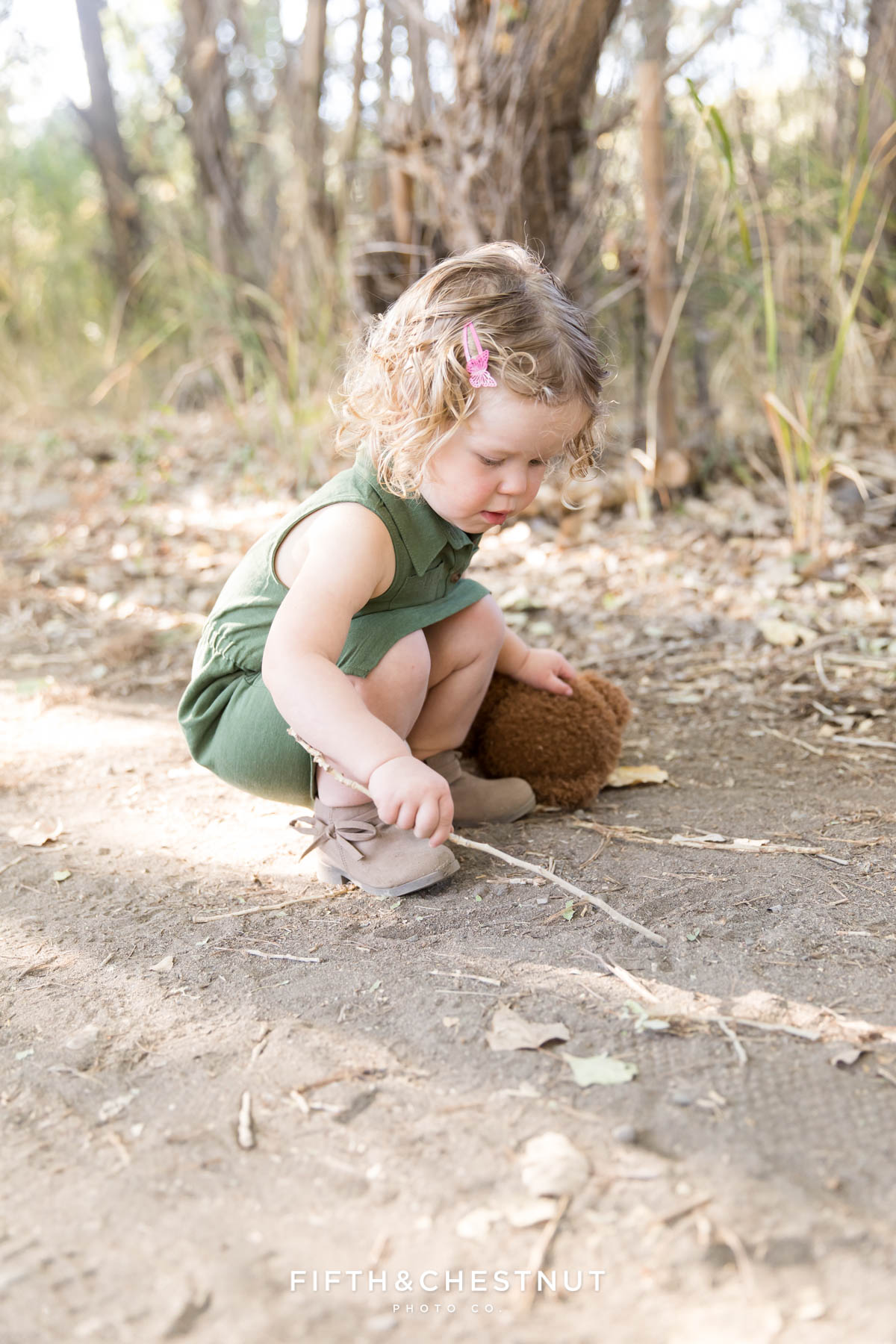 Toddler girl plays in the dirt while wearing a dress