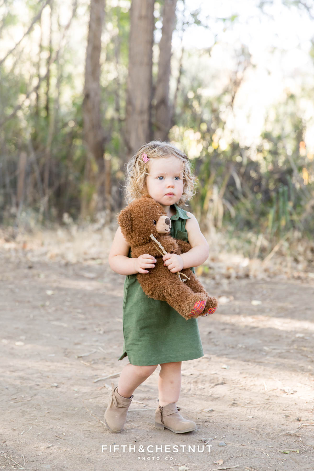 Toddler girl carries a teddy bear and a stick down a dirt path in a green dress.