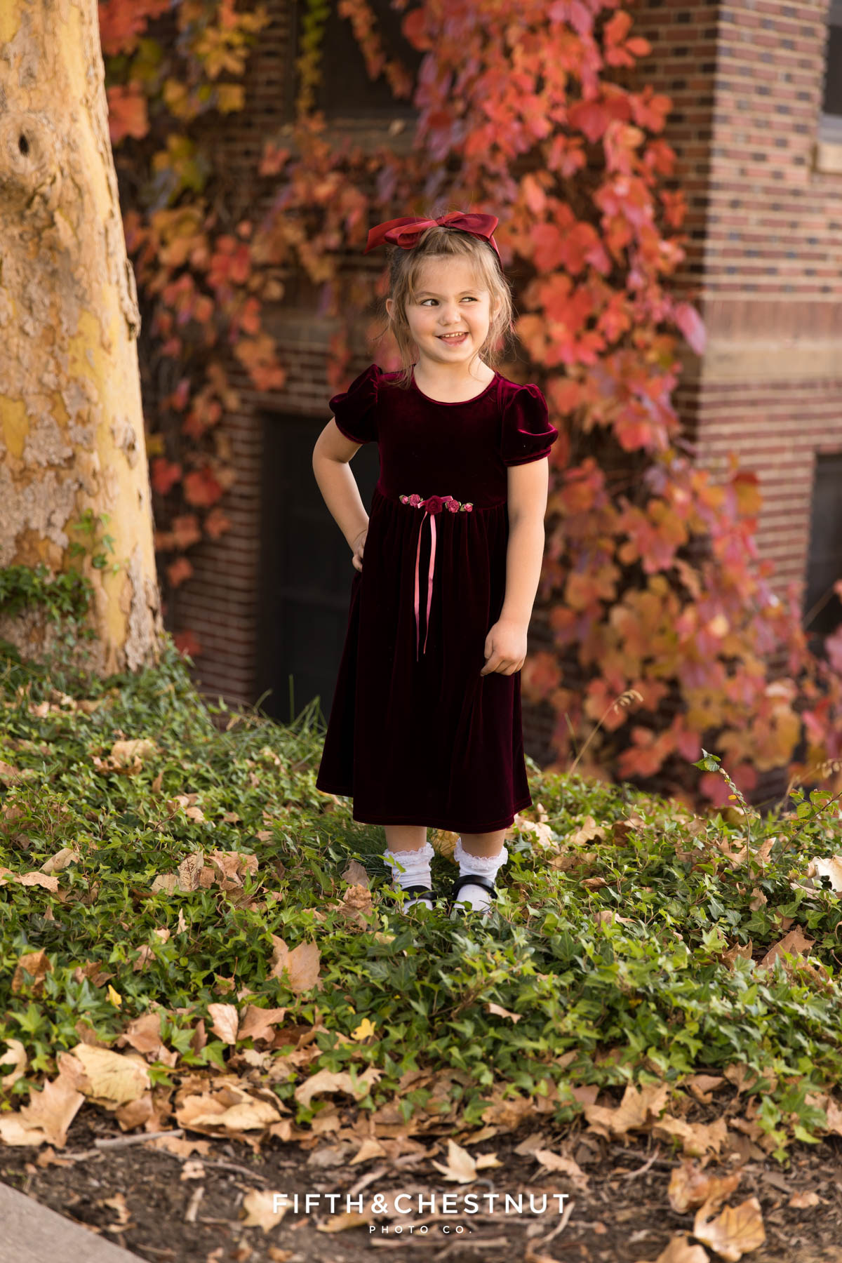 A young girl in a red velvet dress in front of a red ivy wall