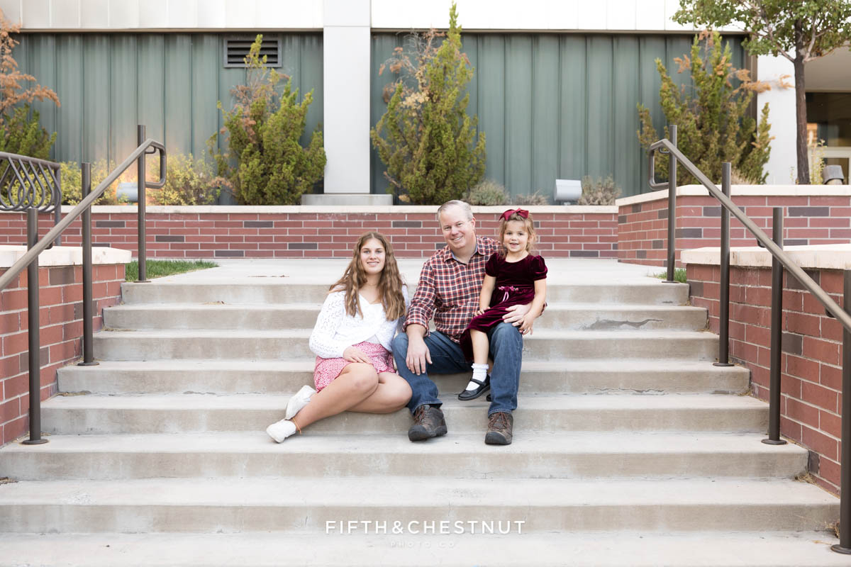 A father and his daughters sit on steps at UNR for family portraits