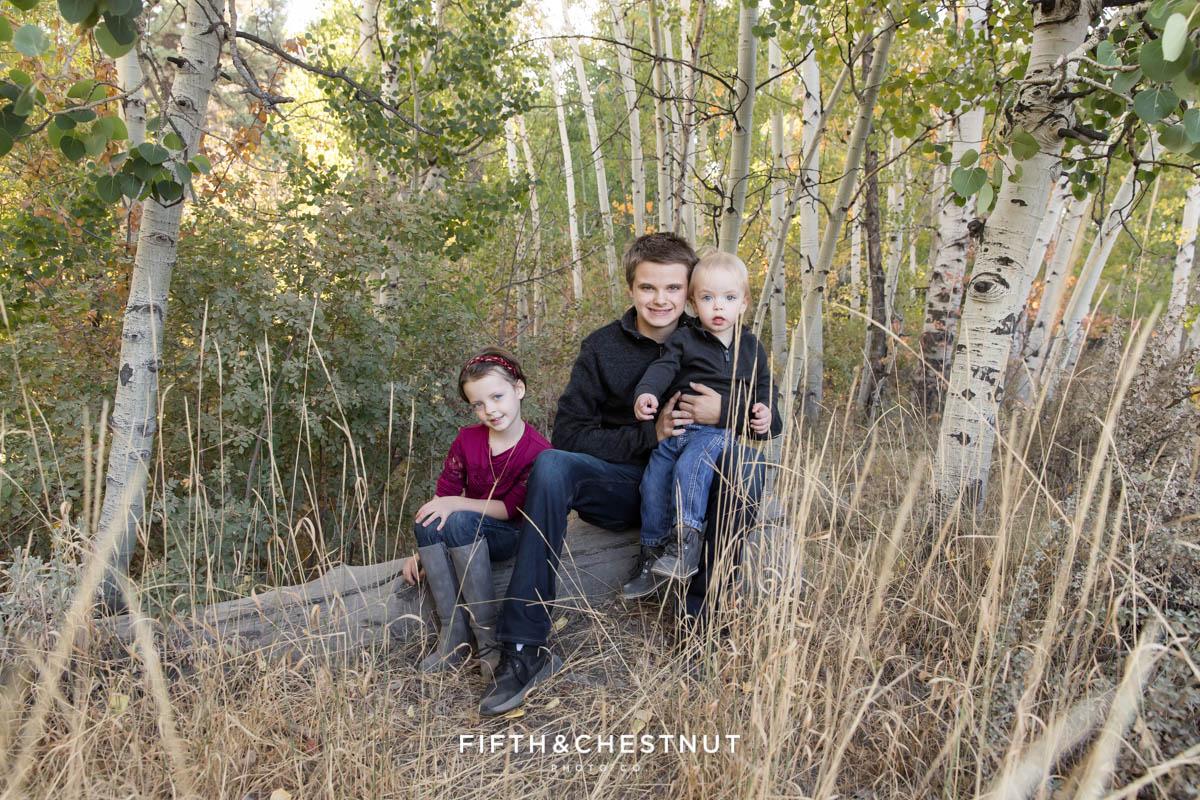 Kids sit together on a log.