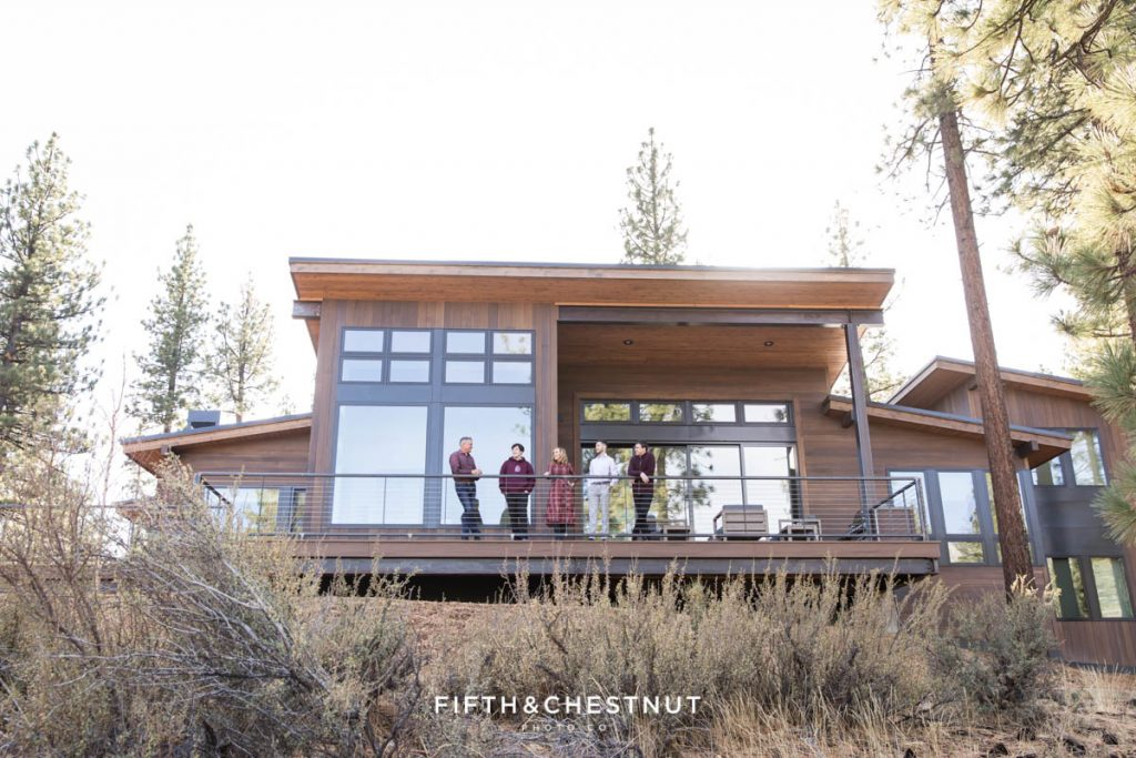 Family of 5 stands on their back balcony overlooking majestic mounatins in the Lake Tahoe foothills