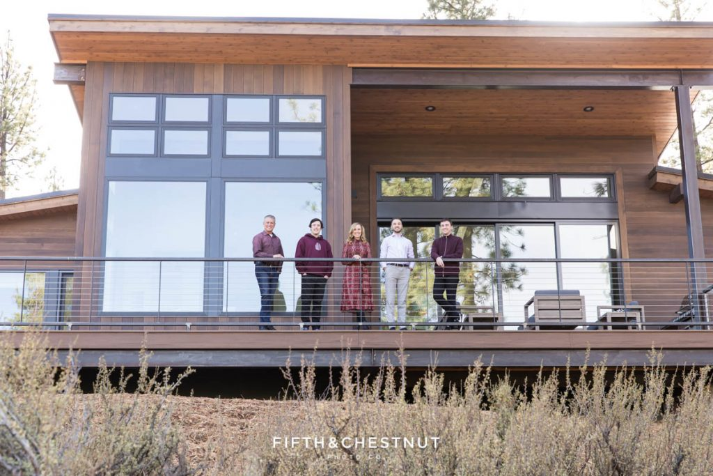 a mountain home stands in the forest and a family poses for a picture with Tahoe Family Photographer Fifth and Chestnut Photo Co.
