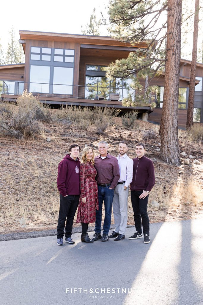 A family dressed in burgundy and black stands together on the street in front of their gorgeous mountain home
