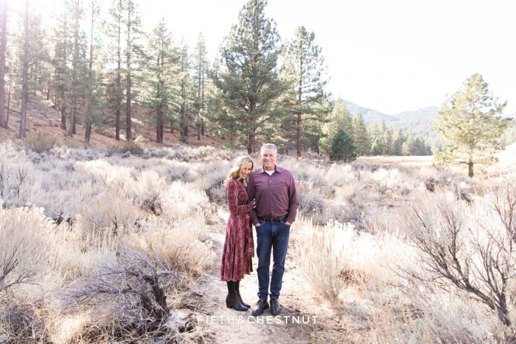 A husband and wife smile on a meadow trail for their tahoe family photographer