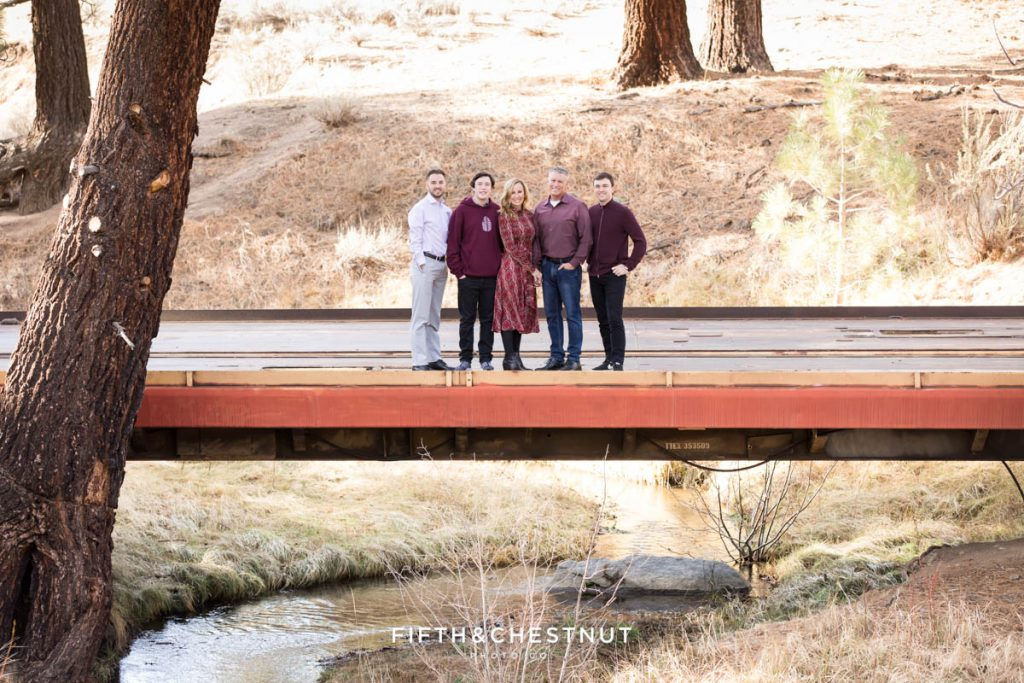 a family stands on a bridge above a small creek that winds through a mountain meadow