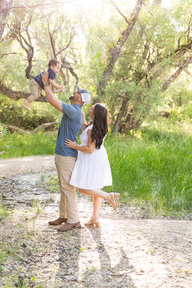 Family of three stands in a lush high desert landscape for their Reno family portraits by Reno Family Photographer