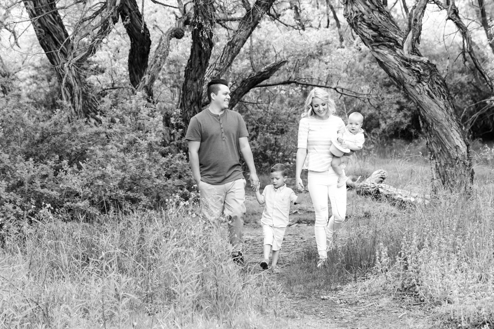 A black and white photo of a beautiful family walking along a wooded path in Reno for their Reno family portraits by Reno Family Photographer Fifth and Chestnut Photo Co.