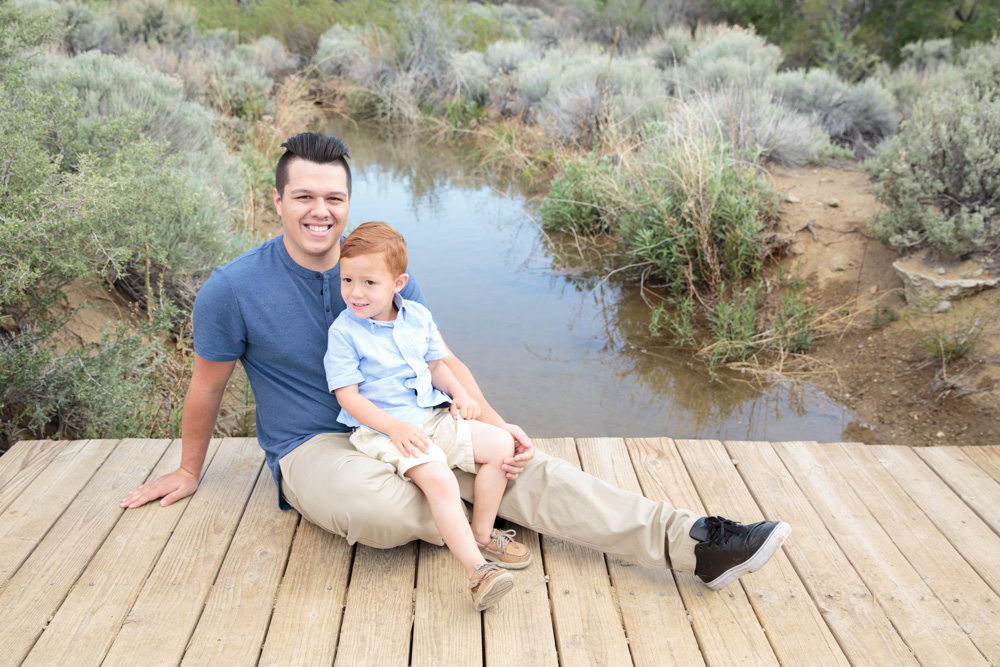 A little boy sits on his father's lap on a wooden bridge at Evan's Creek trail in Reno for a father son picture by Reno Family Photographer