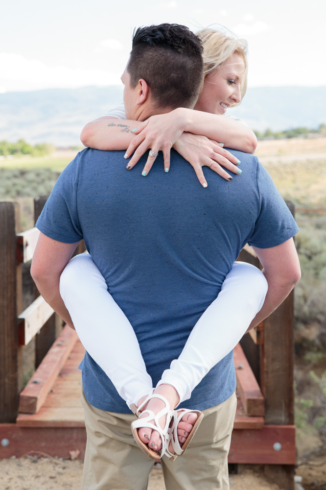 Wife embraces her husband as he carries her with her legs around his waist across a bridge in Reno for a portrait by Reno Family Photographer