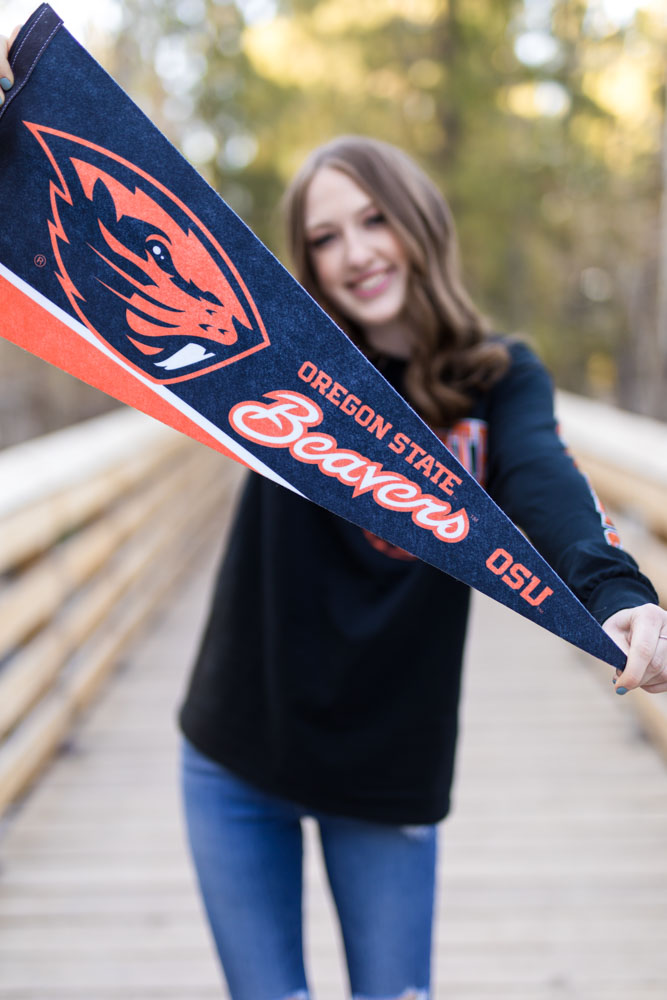 A high school student wearing oregon state gear holds out her banner to celebrate her reno high school photos