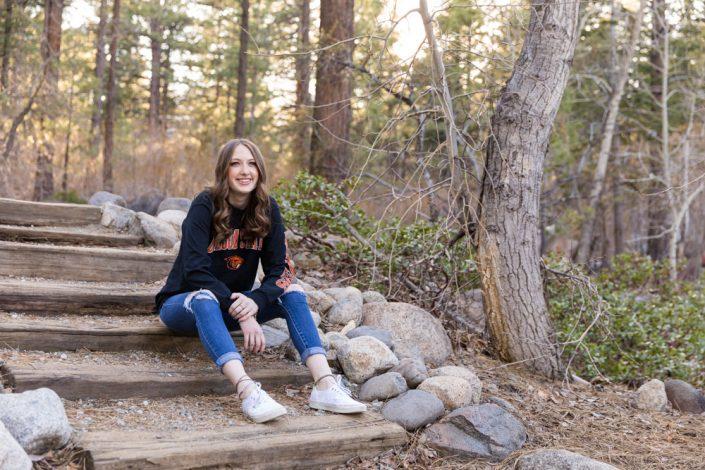 A reno high school senior sits on steps at Galena Creek Park for her reno high school senior portraits