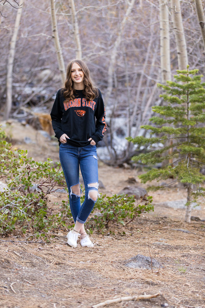 High school senior student stands in the forest in front of manzanita wearing her oregon state shirt