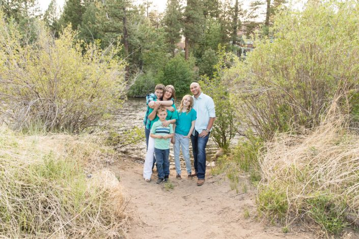 Reno family portraits of a family of five wearing teal and standing in front of the river at Crystal Peak Park with their two dogs for photos by Reno Family Photographer