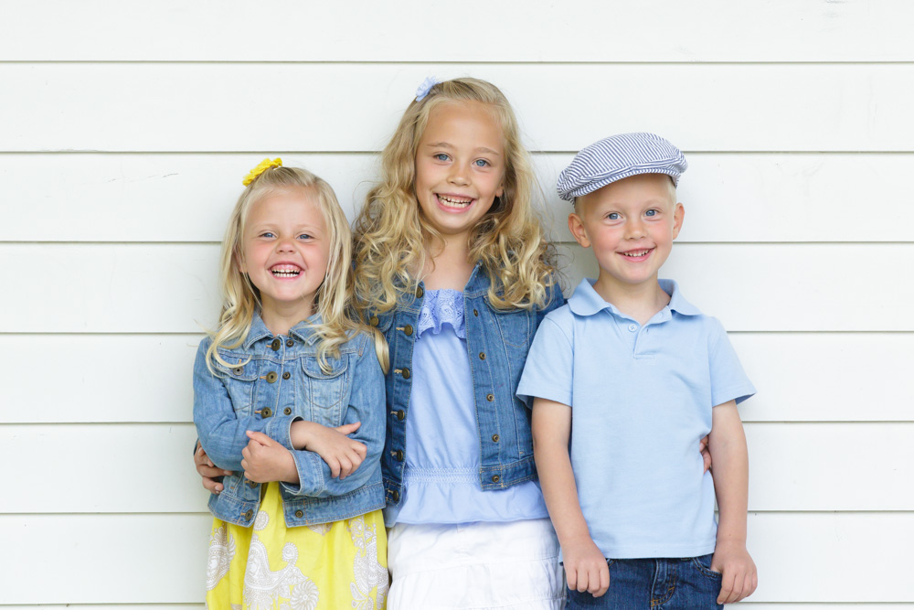 Three young children standing with arms around each other in front a white wooden building for portraits at Bartley Ranch by a Reno Family Photographer