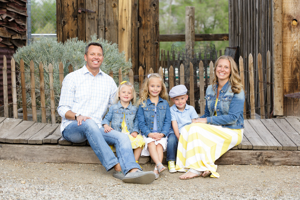 Reno family sitting on a wooden sidewalk along rustic buildings at Bartley Ranch wearing denim and yellow for their yearly Reno family photos taken by Reno Family Photographer