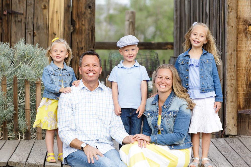 Family of five smiling happily and wearing denim, blue and yellow sitting and standing in front of rustic buildings at Bartley Ranch in Reno for their Reno family portraits by Reno Family Photographer