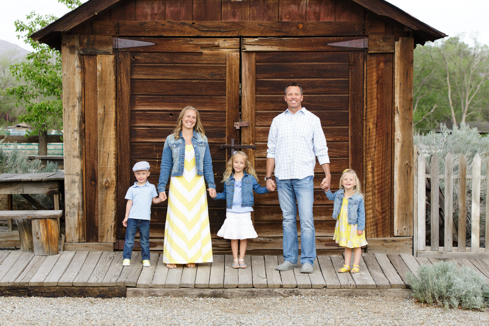 Beautiful family wearing yellow and denim for their family portraits taken by Reno Family Photographer standing in front of an old barn and a wooden picket fence at Bartley Ranch in Reno, NV.