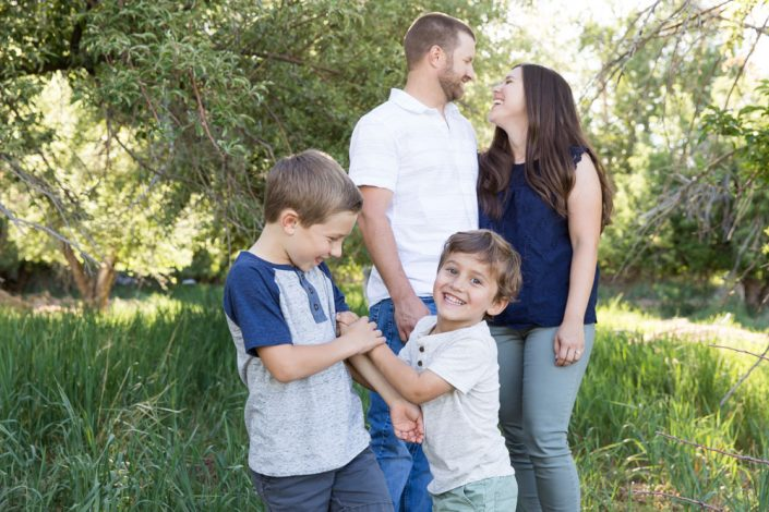 A family of four snuggles together in a lush summer meadow for Reno Family Portraits by Reno Family Photographer