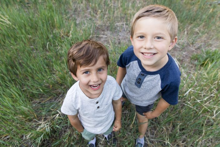 Two boys laugh looking upward into the camera as they stand in a beautiful summer meadow filled with grass