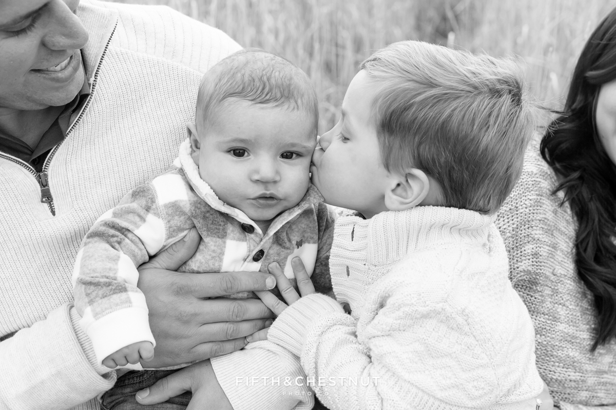 Older brothing kissing baby brother for Holiday Reno Family Portraits in Verdi by Reno Family Photographer