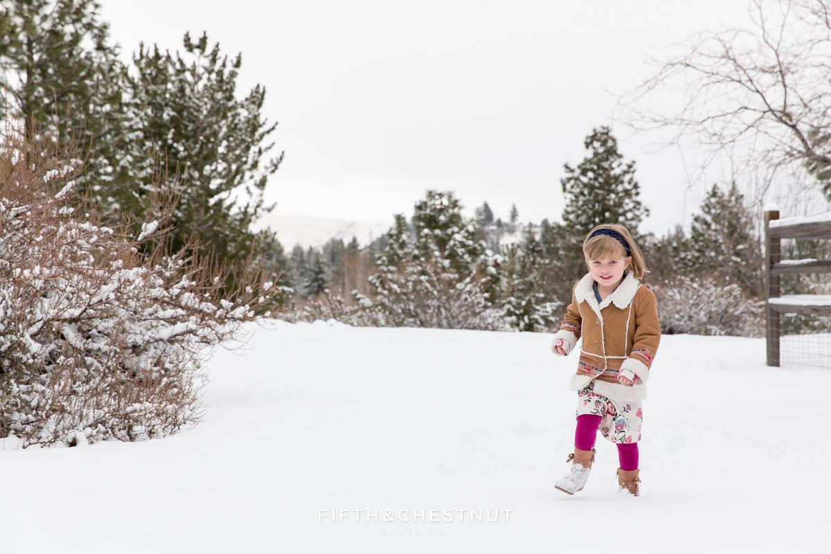 Winter family portrait in Verdi of little girl running through snow