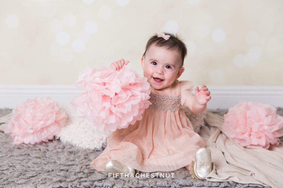 Baby Girl playing with a paper flower and wearing a glittery pink dress for portraits by Reno Baby Photographer Fifth and Chestnut