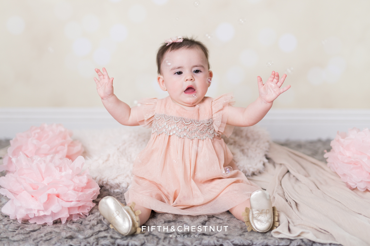 Baby Girl catching bubbles and wearing a glittery pink dress for portraits by Reno Baby Photographer Fifth and Chestnut