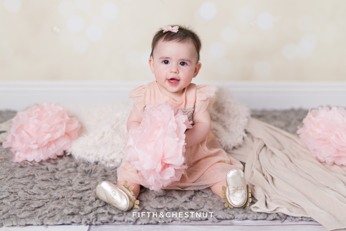Baby Girl smiling and wearing a glittery pink dress for portraits by Reno Baby Photographer Fifth and Chestnut