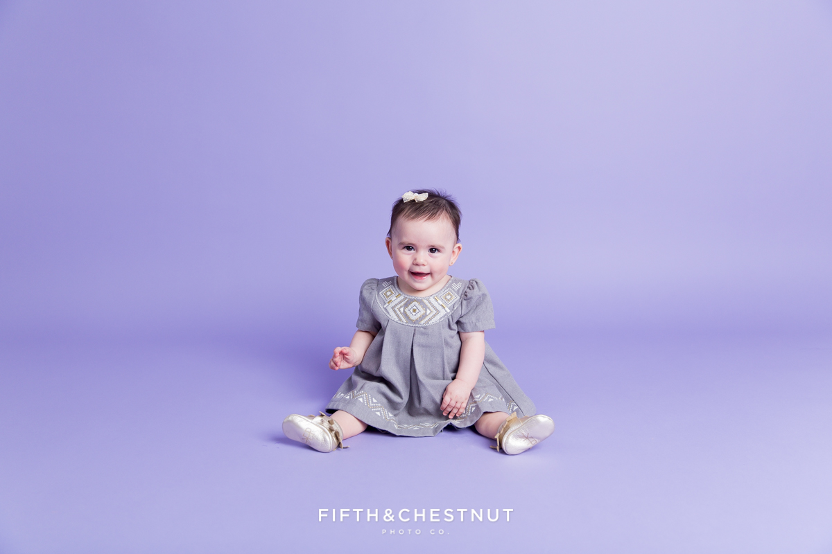 Baby Girl wearing a gray and gold dress for portraits by Reno Baby Photographer Fifth and Chestnut