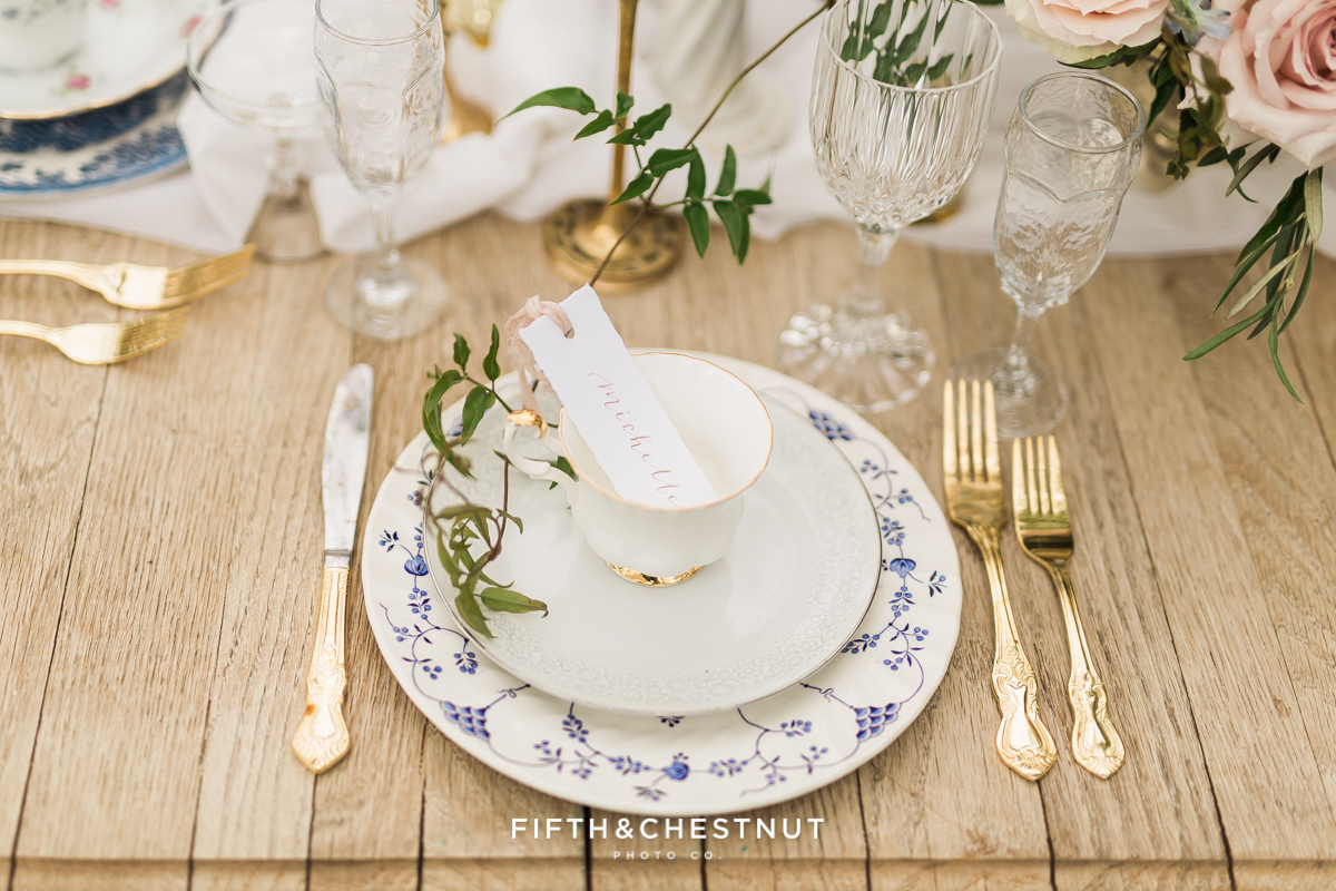 gold flatware and mismatched floral teacups and plates with gold edging for a Dusty Blue Private Estate Country French Wedding Styled Shoot