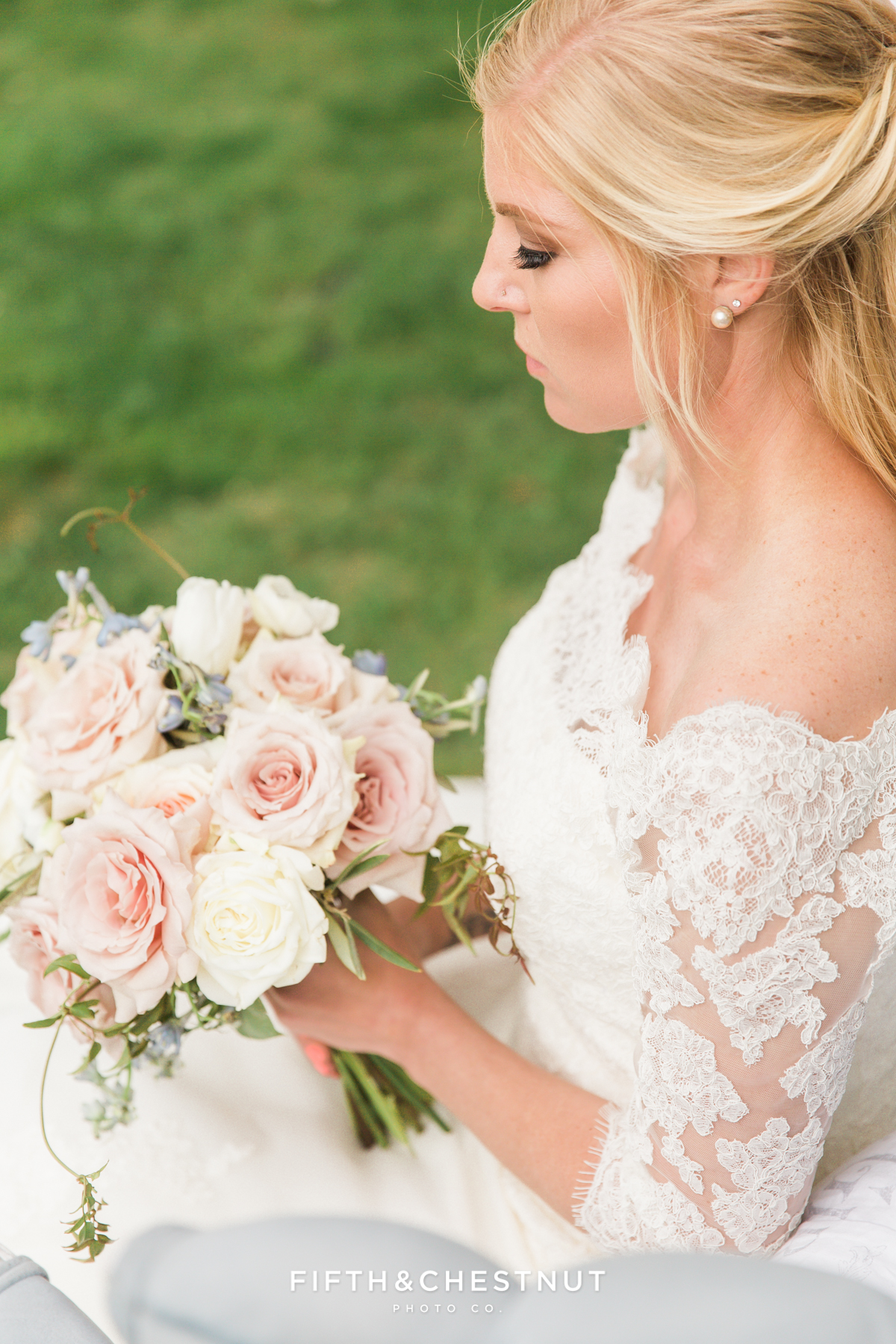 Beautiufl blonde bride looking at her wedding bouquet by Aster and Ash for a dusty blue styled shoot in Reno, NV
