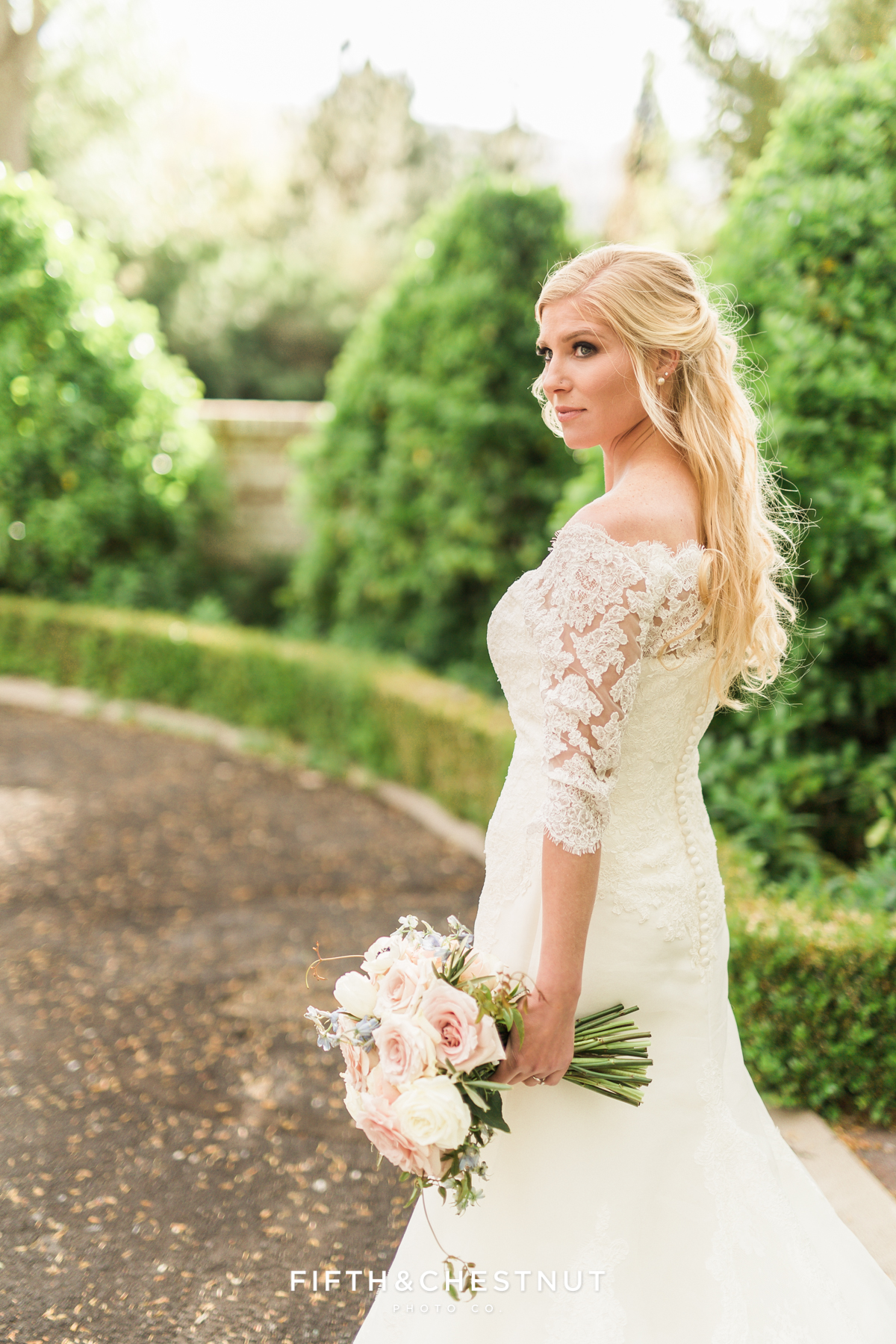 Bride looks into the distance while standing in front of hedges and brick wall