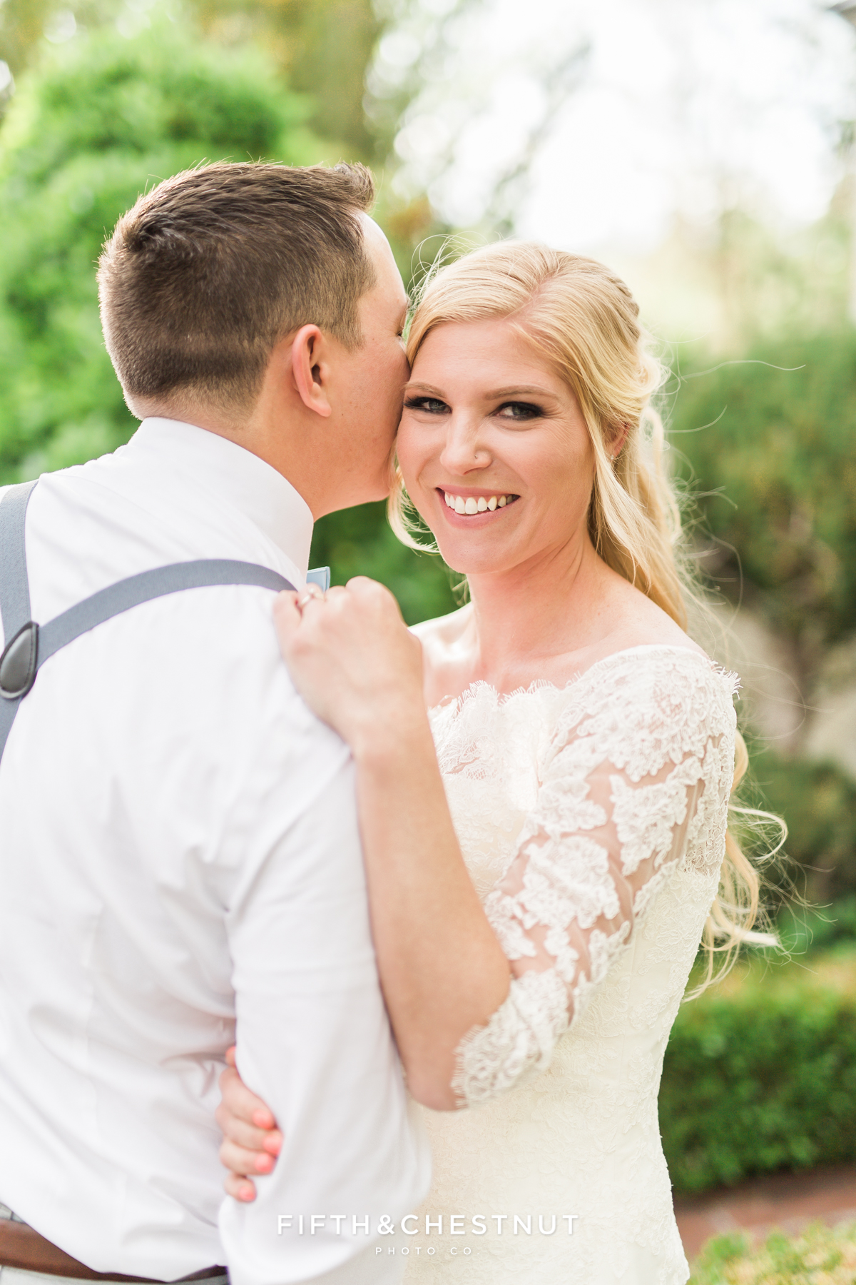 Groom whispering sweet nothings into his brides ear as she smiles and laughs